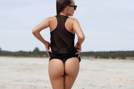 Back view of anonymous lady in lace swimwear touching skin on buttocks while standing near pool on sunny day