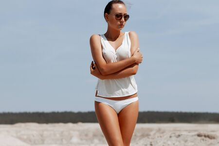 Beautiful young female in knitted panties taking off white blouse while standing near water on resort