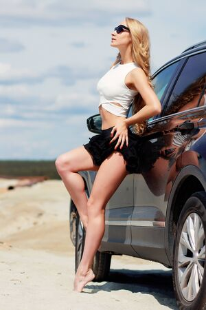 Side view of blonde graceful woman raising leg and leaning on tiptoe on black car looking along Stock Photo