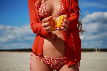 Ripe sliced oranges in hands of seductive charming woman in open swimwear in sandy beach