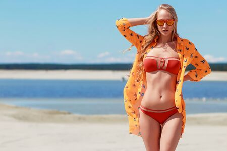Slim sexy woman in red orange swimsuit keeping hair from wind and looking at camera on sandy beach Фото со стока