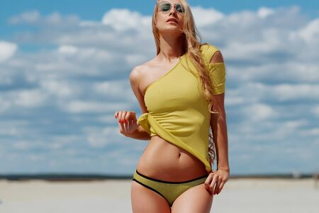 Seductive charming woman with long hair and sun glasses lifting swimsuit exposing belly in sandy beach on background of cloudy sky Фото со стока