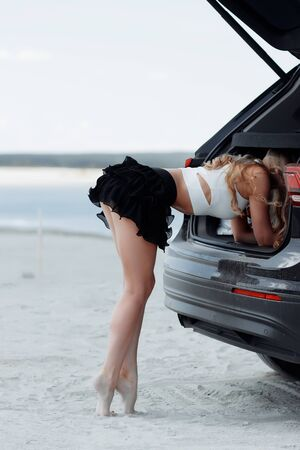 Side view of blonde graceful woman raising leg and leaning on tiptoe on black car looking along Фото со стока