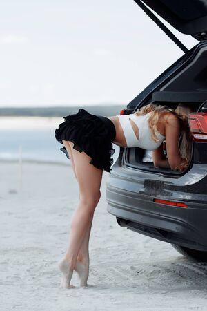 Vista laterale della donna graziosa bionda che alza la gamba e si appoggia in punta di piedi su un'auto nera che guarda lungo Archivio Fotografico