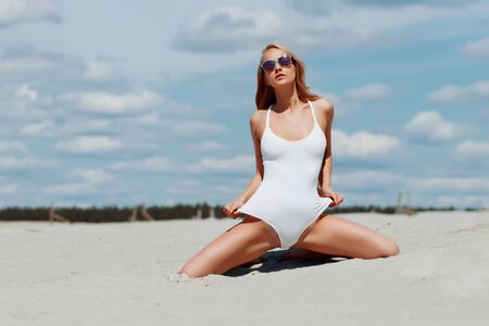 Young skinny sexy long haired woman in perfect white swim suit kneeling on beach with hands up and looking at camera