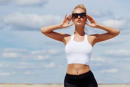Tanned sporty woman in sunglasses throwing hands gracefully behind head and languidly enjoying sandy beach