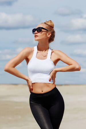 Gebräunte sportliche Frau mit Sonnenbrille, die Hände anmutig hinter den Kopf wirft und träge den Sandstrand genießt