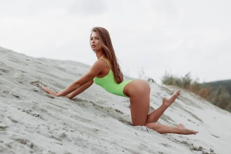 Skinny long haired sexy woman posing in seductive energetic posture in sandy beach on background of cloudy sky Imagens
