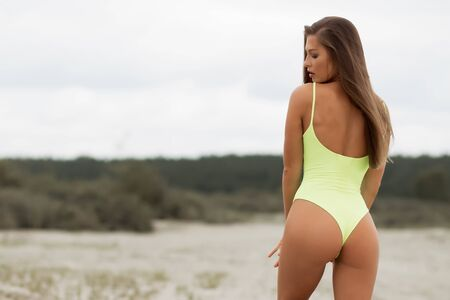Beautiful young female in yellow swimsuit