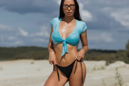 Seductive pretty woman in blue crop top and black panties standing on sandy beach and looking at camera