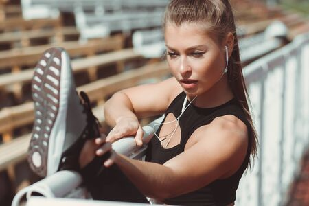 Side view of fit athletic female in sportswear and with headphones warming up while leaning on fence on urban sports ground