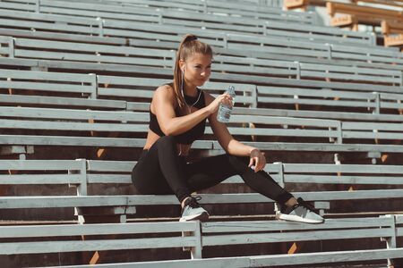 Athletic woman in sportswear and earphones listening to music and drinking water from bottle while sitting on bleachers on athletic field Stockfoto