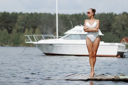 Slim woman wearing white bathing suit and sunglasses standing on wooden pier with yacht on background Imagens