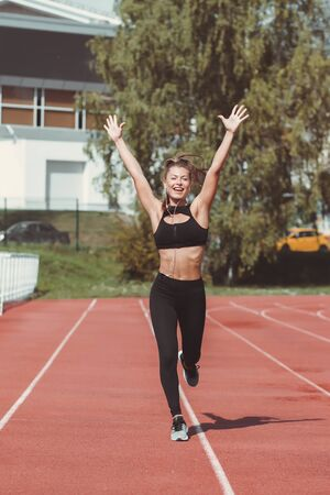 Excited fit female runner in sportswear and with headphones holding arms raised while jogging happy along lane on sports ground