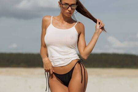 Crop woman standing in white tank top and black bikini panties and looking down on blurred nature background