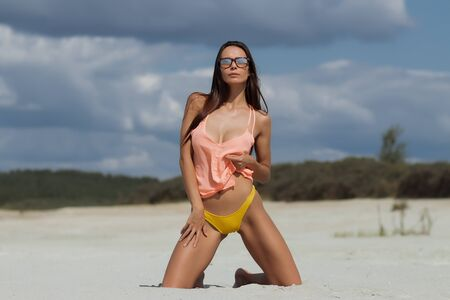 Attractive young female in top and panties closing eyes and touching hair while standing on knees on sandy beach against cloudy sky on resort Imagens