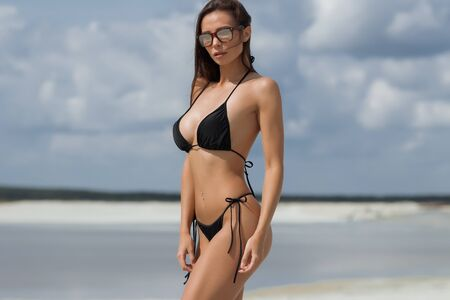 Gorgeous tanned woman in sunglasses dressed in swimsuit standing on beach near sea looking at camera