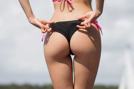 Back view of slim sexy woman in sunglasses taking off swimsuit panties on background of yacht Zdjęcie Seryjne