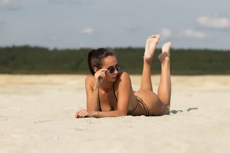 Side view of sensual alluring woman in camouflage bikini lying provocatively on sandy beach and looking above