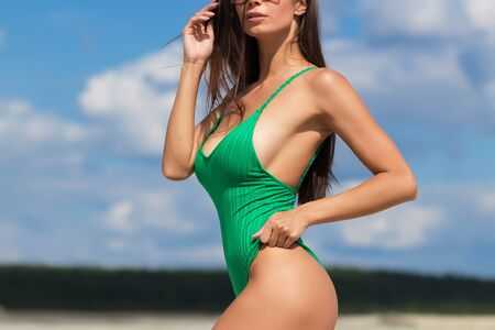 Crop alluring female in green bathing suit standing with hand on waist showing curvy body in sunlight