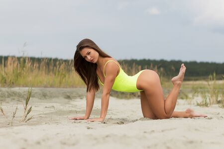 Gorgeous young female crawling on beach