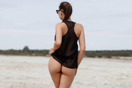 Sensual slim female in black swimsuit on beach Zdjęcie Seryjne