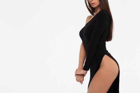 Vue latérale d'une dame sensuelle en robe noire regardant la caméra sur fond blanc Banque d'images