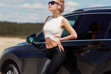Side view of skinny graceful woman in black trousers and sun glasses nearby black car looking along