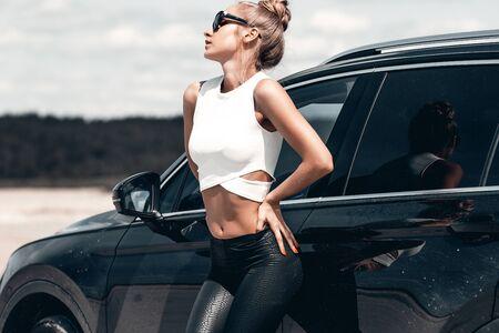 Vista laterale di una donna magra e graziosa in pantaloni neri e occhiali da sole nelle vicinanze di un'auto nera che guarda lungo