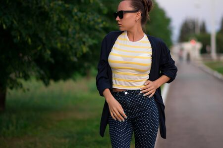 Attractive calm slim female in yellow and white striped shirt and blue with white polka dots pants in composition with unbuttoned blue jacket standing with hands in pockets and looking away against blurred summer park Archivio Fotografico