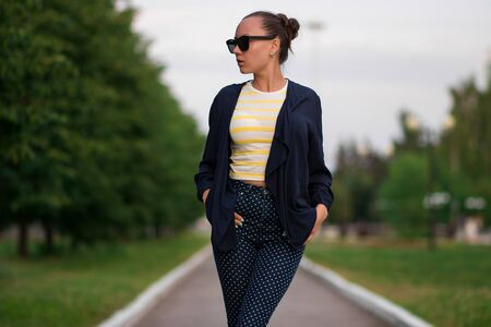 Attractive calm slim female in yellow and white striped shirt and blue with white polka dots pants in composition with unbuttoned blue jacket standing with hands in pockets and looking away against blurred summer park