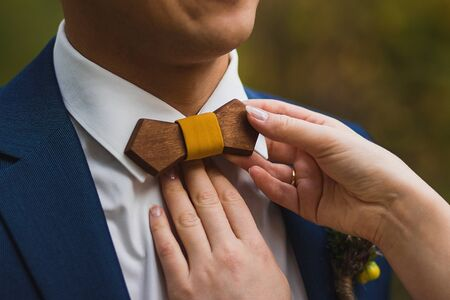 Crop caring wife straightening trendy wooden bow tie with yellow fabric knot to husband in elegant white shirt and blue jacket against green blurred background Stock Photo - 133539315