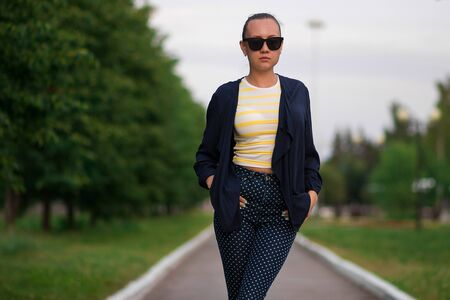 Attractive calm slim female in yellow and white striped shirt and blue with white polka dots pants in composition with unbuttoned blue jacket standing with hands in pockets and looking away against blurred summer park Stock fotó