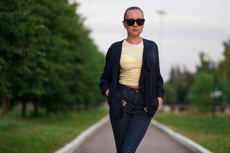 Jolie femme mince et calme en chemise rayée jaune et blanche et bleu avec un pantalon à pois blancs en composition avec une veste bleue déboutonnée debout avec les mains dans les poches et regardant au loin contre un parc d'été flou Banque d'images