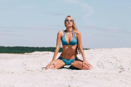 Dünne langhaarige Frau mit Sonnenbrille posiert in verführerischer energetischer Haltung am Sandstrand auf dem Hintergrund des bewölkten Himmels
