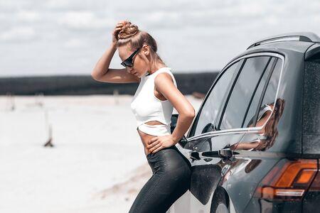 Bella donna appoggiata alla macchina sulla strada