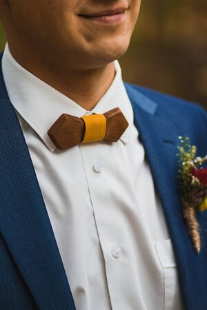 Caring bride straightening wooden bow tie to groom