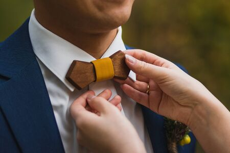 Crop caring wife straightening trendy wooden bow tie with yellow fabric knot to husband in elegant white shirt and blue jacket against green blurred background Stock Photo - 133539382