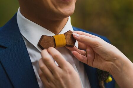 Crop caring wife straightening trendy wooden bow tie with yellow fabric knot to husband in elegant white shirt and blue jacket against green blurred background Stock Photo - 133539381