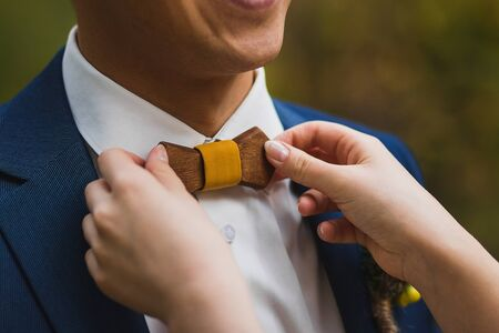 Crop caring wife straightening trendy wooden bow tie with yellow fabric knot to husband in elegant white shirt and blue jacket against green blurred background Stock Photo - 133539425