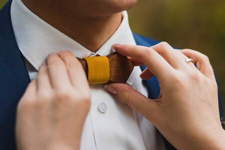Crop caring wife straightening trendy wooden bow tie with yellow fabric knot to husband in elegant white shirt and blue jacket against green blurred background Stock Photo - 133539432