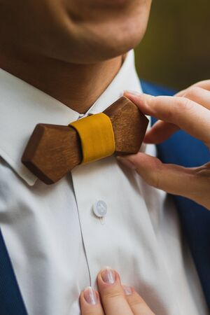 Crop caring wife straightening trendy wooden bow tie with yellow fabric knot to husband in elegant white shirt and blue jacket against green blurred background Stock Photo - 133539439