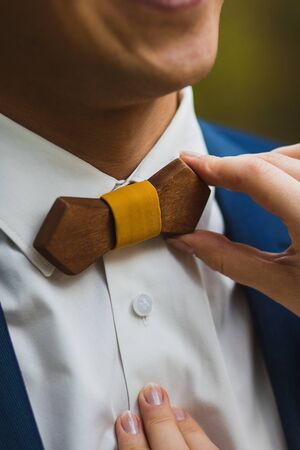 Crop caring wife straightening trendy wooden bow tie with yellow fabric knot to husband in elegant white shirt and blue jacket against green blurred background Stock Photo - 133539446