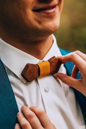 Crop caring wife straightening trendy wooden bow tie with yellow fabric knot to husband in elegant white shirt and blue jacket against green blurred background Stock Photo - 133539452