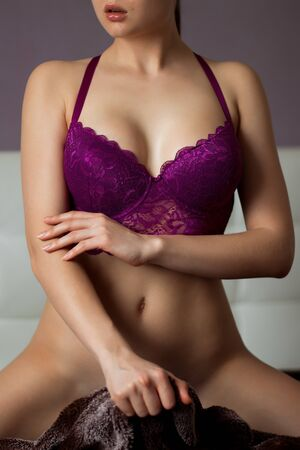 Crop unrecognizable sensual young female in beautiful violet lace bra with closed arms and raised shoulders indoors