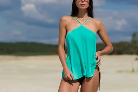 Provocative young lady in spectacles crumpling stylish top and looking away while standing on beach on cloudy day on resort Stock fotó