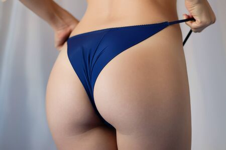 Unrecognizable seductive female in thongs showing perfect bottom while standing near window at home Standard-Bild