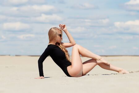 Plastic woman in sunglasses and black swimwear gracefully sitting stretching legs on sandy beach in picturesque day