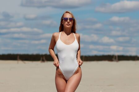Graceful seductive woman in white swimsuit and sunglasses enjoying weather and comfort lingerie