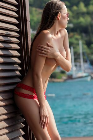 Side view of sensual young female in red knitted swimsuit putting bra and leaning on wall of building near calm water on sunny day